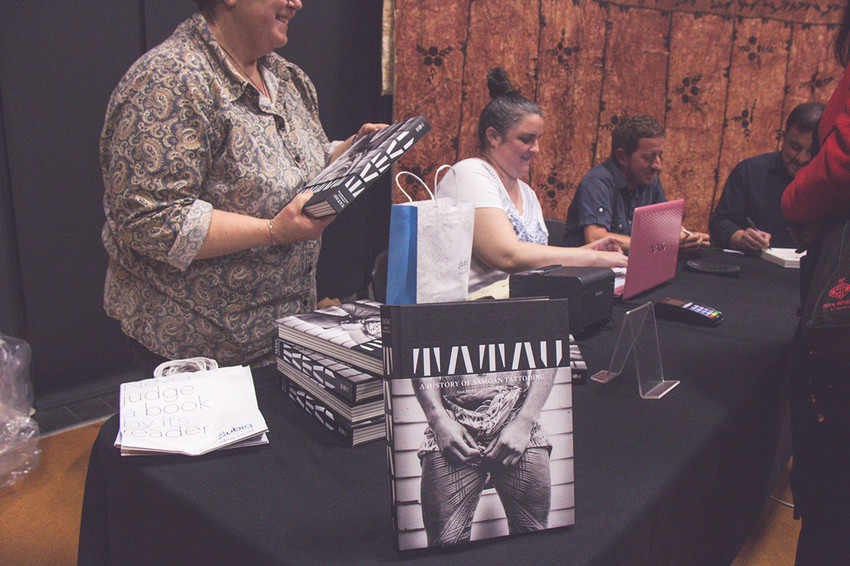 Signing books at the book launch and seminar at Auckland University