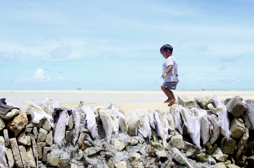 Child walks over a makeshift seawall built in Kiribati